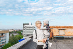 Portrait of young mother and daughter travellers standing on city roof Stock Photos