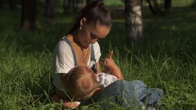 Portrait of young mother feeding baby in park, sitting on ground. Woman being playful with child while breastfeeding