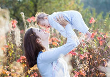 Portrait of young mother with her baby in sunny park Stock Photography