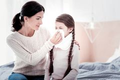 Portrait of young mother with her daughter blowing her nose stock photos
