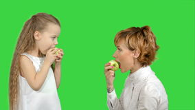 Portrait of a young mother and her little daughter eating apples on a green screen, chroma key stock footage