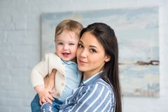Portrait of young mother holding cheerful adorable baby boy. In hands at home royalty free stock images