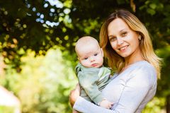 Portrait of young mother holding cute baby royalty free stock photos