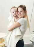 Portrait of young mother holding her baby after having bath. Portrait of happy young mother holding her baby after having bath Stock Image