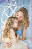 Portrait of Young mother holds her little daughter on a chair Royalty Free Stock Image