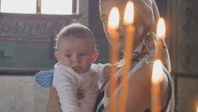 Portrait of young mother with little son in front of candles in church stock footage
