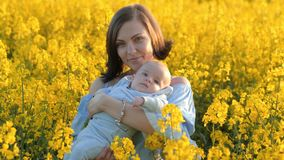 Portrait of young mother with newborn baby having fun in yellow field. Love, family, joy concept stock video footage