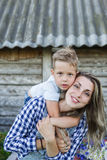 Portrait of young mother with son standing together in front of old retro wooden house Stock Photos