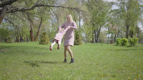 Portrait young mother spinning the daughter on hands on nature on spring day. Woman and kid playing in the park. Joking. And having fun. Family vacation in the stock video footage