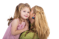 Portrait of young mother whispering secrets in her  adorable dau Royalty Free Stock Image