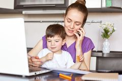 Portrait of young mother works freelance on laptop computer, communicates with someone via smart phone, looks after her little son. Who doesn`t go to royalty free stock photo