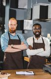 Portrait of young multicultural owners of coffee shop in aprons standing with crossed arms. In coffee shop stock photo