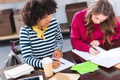 Portrait of young multicultural students doing. Homework together stock image