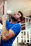 Portrait of young muscular athlete climbing fitness rope in spor Stock Images