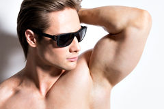 Portrait of young muscular sexy man in glasses. Royalty Free Stock Images