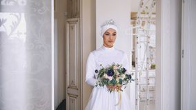Portrait of young muslim bride with professional make up in white dress with flowers. Horizontal Stock Photo