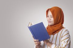 Muslim Businesswoman Reading Book. Portrait of young muslim businesswoman wearing hijab reading book indonesian malay female adult girl corporate attractive stock photo