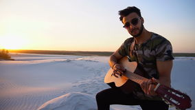 Portrait of young Muslim man who plays music on guitar among sandy desert at sunset in open air on summer evening. Handsome Arabian guy plays tune on guitar stock video footage