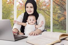 Muslim mother working with her baby at home Royalty Free Stock Photos