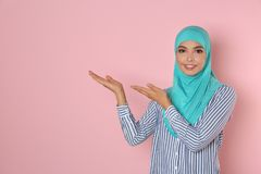 Portrait of young Muslim woman in hijab against color background royalty free stock photos