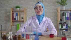 Portrait young muslim woman scientist chemist in national scarf working in the lab. And looks at the camera stock video footage