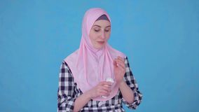 Portrait young Muslim woman uses face cream. Close up blue isolate background stock video