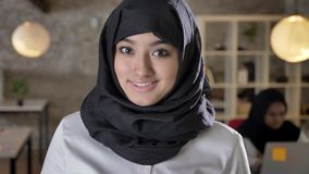 Portrait of young muslim women in hijab looking into camera, smiling, two womens working in modern office.  stock video footage