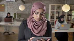 Portrait of young muslim women in hijab standing with tablet, looking in camera, smiling, business womens typing on. Laptop in office stock video footage