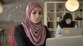 Portrait of young muslim women in hijab working and looking in camera, two womens sitting and typing on laptop in modern. Office stock footage