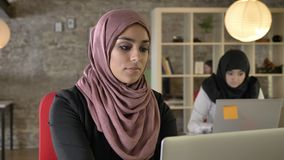 Portrait of young muslim women working, serious, two womens in hijab sitting and typing on laptop in modern office. Concentrated stock footage