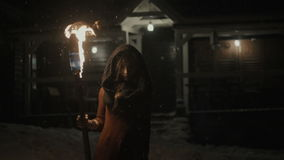 Portrait of a young mystic woman in the dark holding a torch. Young woman with torch over dark night background. Pretty woman standing in front of her house in