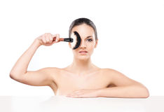 Portrait of a young and naked Caucasian woman with a makeup brush Stock Image