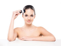 Portrait of a young and naked Caucasian woman with a makeup brush Stock Photography
