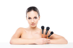 Portrait of a young and naked Caucasian woman with a makeup brush Stock Images