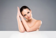 Portrait of a young and naked woman on grey Stock Images