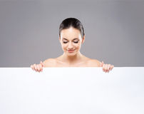 Portrait of a young naked woman holding a banner Stock Photo