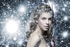 Portrait of a young naked woman on a snow background Stock Image