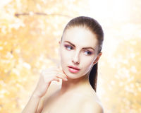 Portrait of young, natural and healthy woman over yellow autumn background. Healthcare, spa, makeup and face lifting concept Stock Photo
