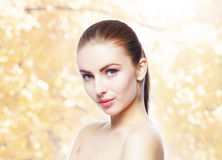 Portrait of young, natural and healthy woman over yellow autumn background. Healthcare, spa, makeup and face lifting concept Stock Images