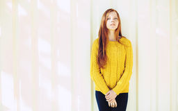Portrait of a young naughty redhead woman in yellow sweater against an  urban texture background Stock