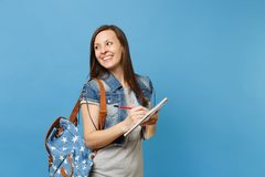 Portrait of young nice joyful woman student in denim clothes with backpack looking aside writing notes on notebook royalty free stock photography