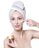Portrait of the young nice woman with a white towel on the head putting cosmetic cream on a face on a white background Stock Image