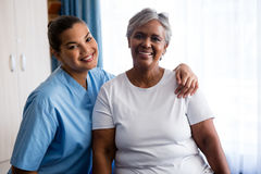 Portrait of young nurse with patient in nursing home. Portrait of young nurse with senior patient in nursing home Royalty Free Stock Photos
