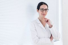 Portrait of a young nurse or physician looking at camera with confidence. Portrait of a young nurse or physician wearing eyeglasses and white medical gown while royalty free stock photos