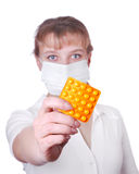 Portrait of young nurse in surgeon's cap. And mask holds pill in her hand. Focus to hand and pill Stock Photo