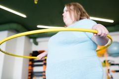 Obese Woman with Hula Hoop. Portrait of young obese woman working out with hula hoop in fitness club, focus on foreground Stock Images