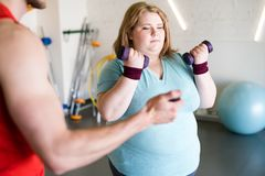 Obese Woman Working Out  with Weights. Portrait of young obese women training with dumbbells while personal instructor timing her in gym Stock Photos