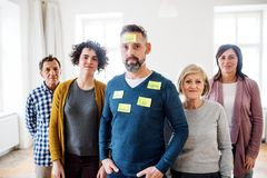 Young and old people standing with negative emotions adhesive notes during group therapy. A portrait of young and old people standing with negative emotions stock photography