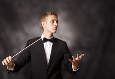 Portrait of a young orchestra conductor. Portrait shot of a young orchestra conductor directing with his baton in a classical concert Stock Photography