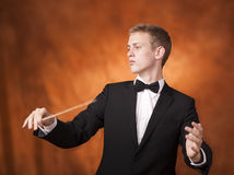 Portrait of a young orchestra conductor. Portrait shot of a young orchestra conductor directing with his baton in a classical concert Stock Photos